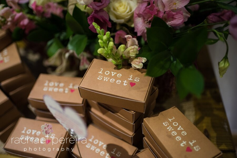 "How sweet are these little ""Love is Sweet"" cake boxes!  They were all stacked up on the table in the entrance hall ready for the guests to take home with them."
