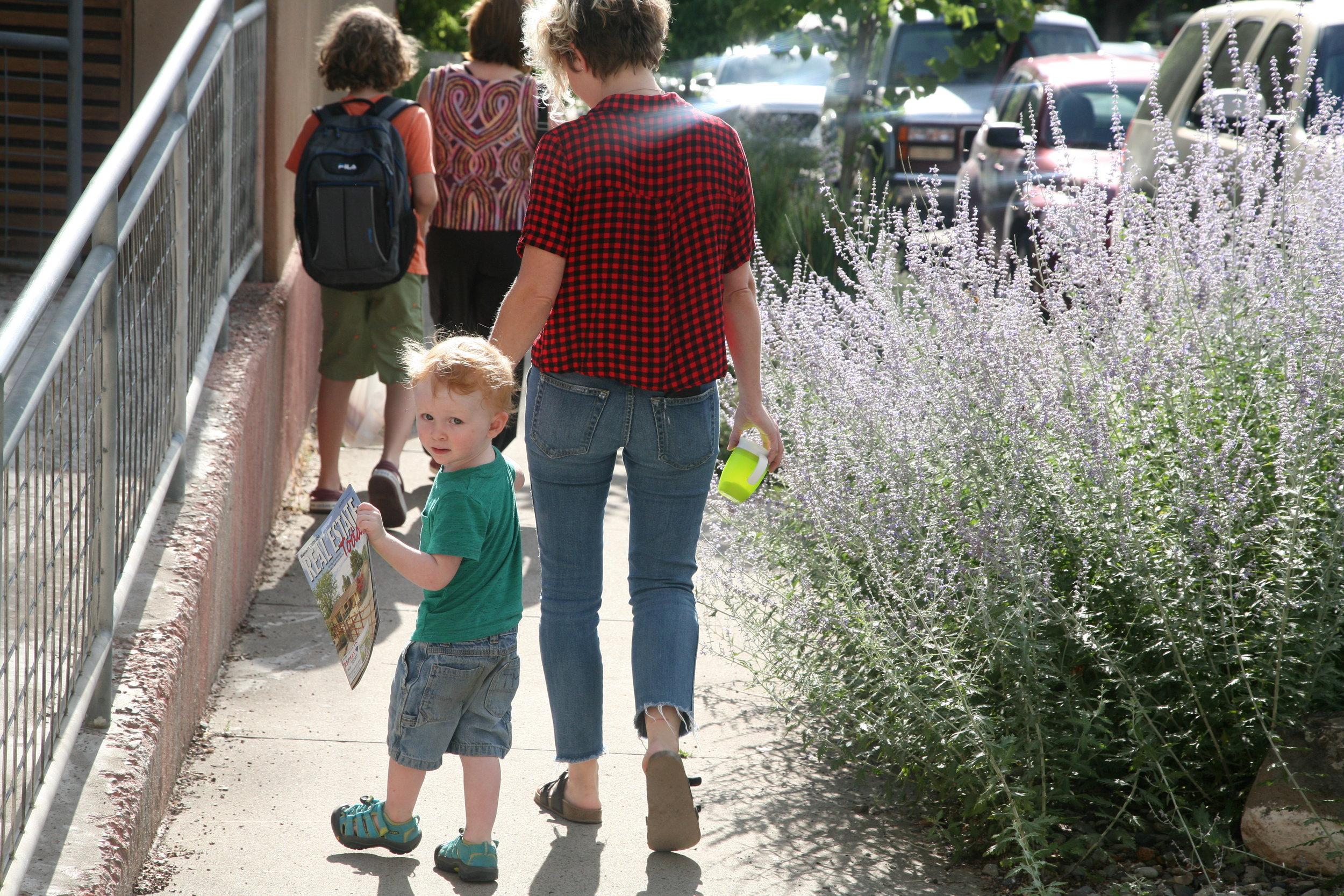 Brigid's son, Sebi, walking with friend and babysitter, Hanna Doreen Brown behind Resident Maria Velasco and son Alex.