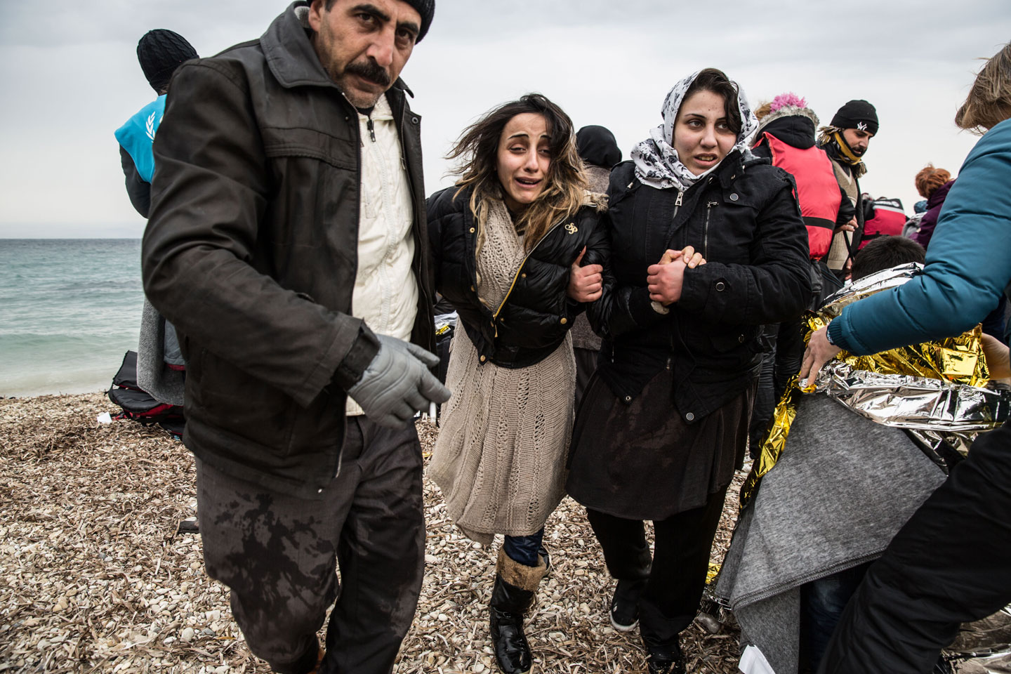 photographer: Hereward Holland |A family of refugees help a distressed woman ashore on the Greek island of Lesvos.