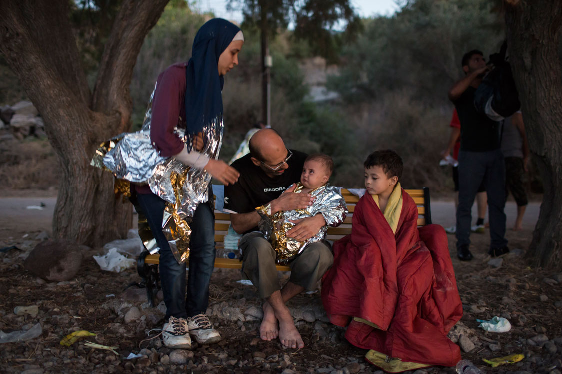 Photographer: Ivor Prickett |Syrian refugee's Omar and Asmaa try to comfort their 6-month old baby Osman while her 5-year-old boy Abdul-Rahman sits beside them. Asmaa and her husband Omar fled their home near Damascus over one and half months ago, travelling through Lebanon then onto Turkey before crossing the Aegean to Greece. The boat they were travelling was heavily overloaded and when the engine cut out they began to take water on-board. In a bid to stay afloat everyone decided to throw their luggage overboard.