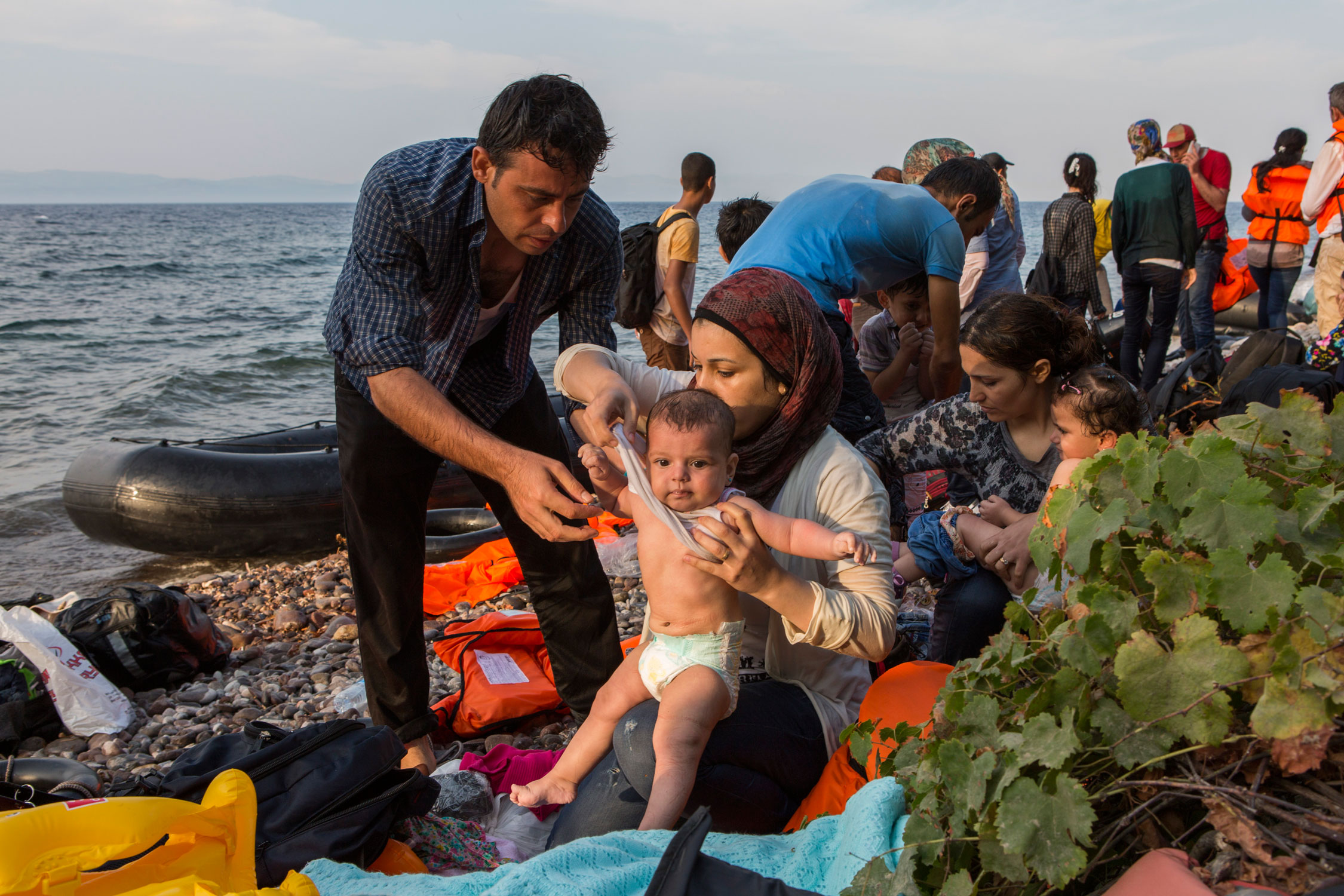 Photographer: Ivor Prickett | A Syrian couple change their baby out of its wet clothes after a very rough crossing across the Aegean from Turkey to the Greek island of Lesbos.