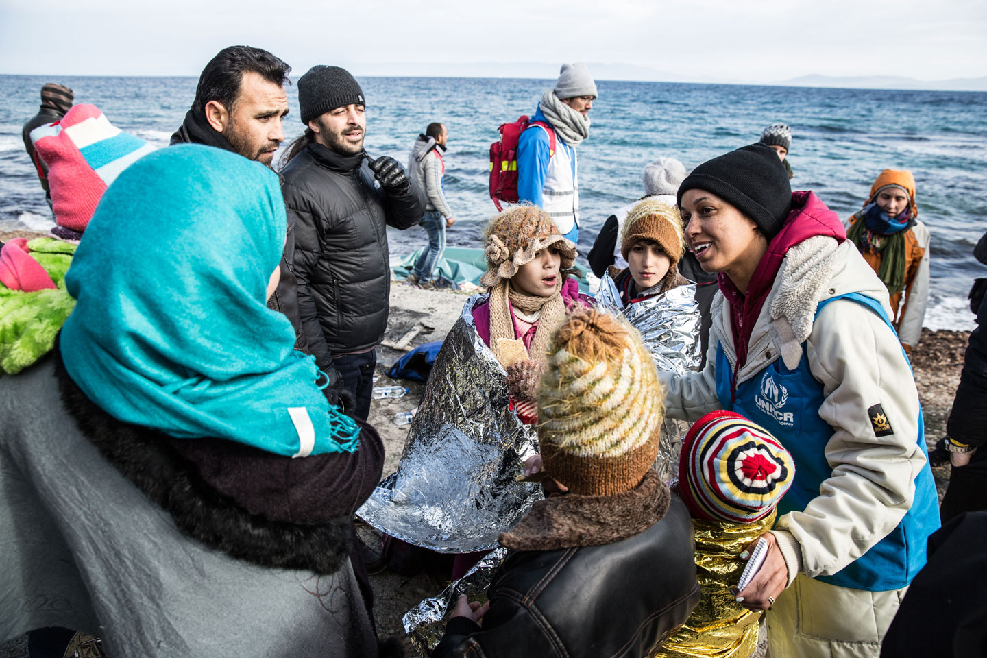 Photographer: Hereward Holland |A UNHCR staff member talks to a family of refugees who have just arrived on the Greek island of Lesbos after crossing the short stretch of sea from Turkey.