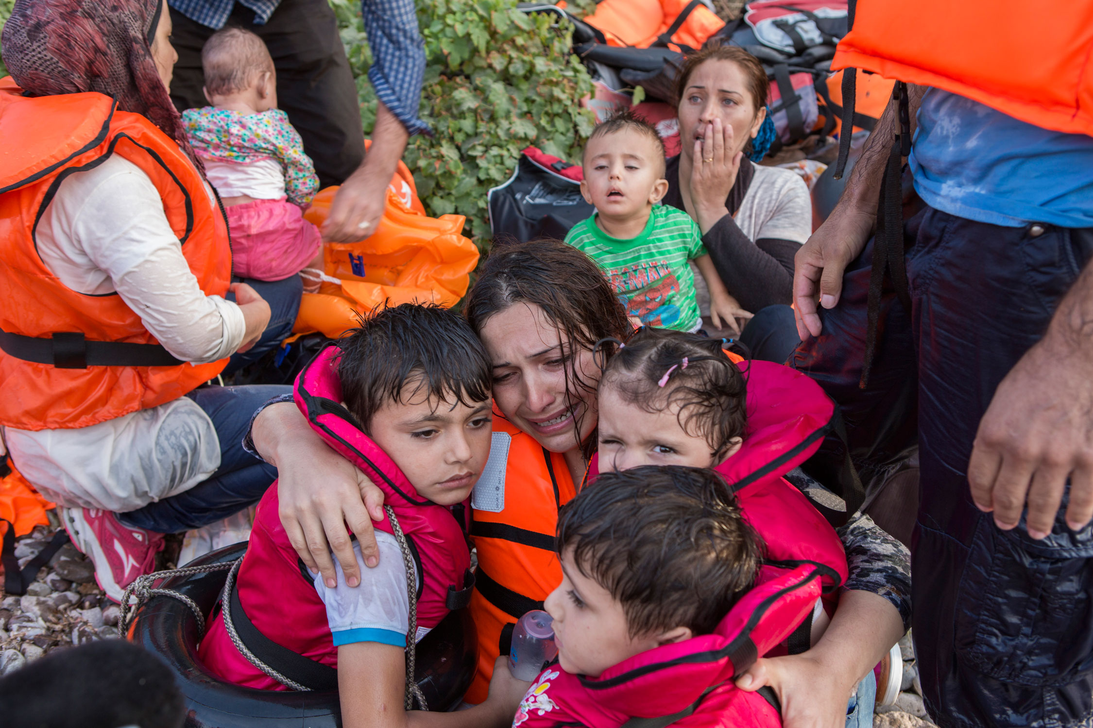 Photographer: Ivor Prickett | A Syrian woman cries in relief as she embraces her three young children. They have just endured a very rough crossing across the Aegean from Turkey to the Greek island of Lesbos.  Women and children currently account for two thirds of those crossing to Europe. In February 2016, they made up nearly 60 per cent of sea arrivals, compared to 27 per cent in September 2015.