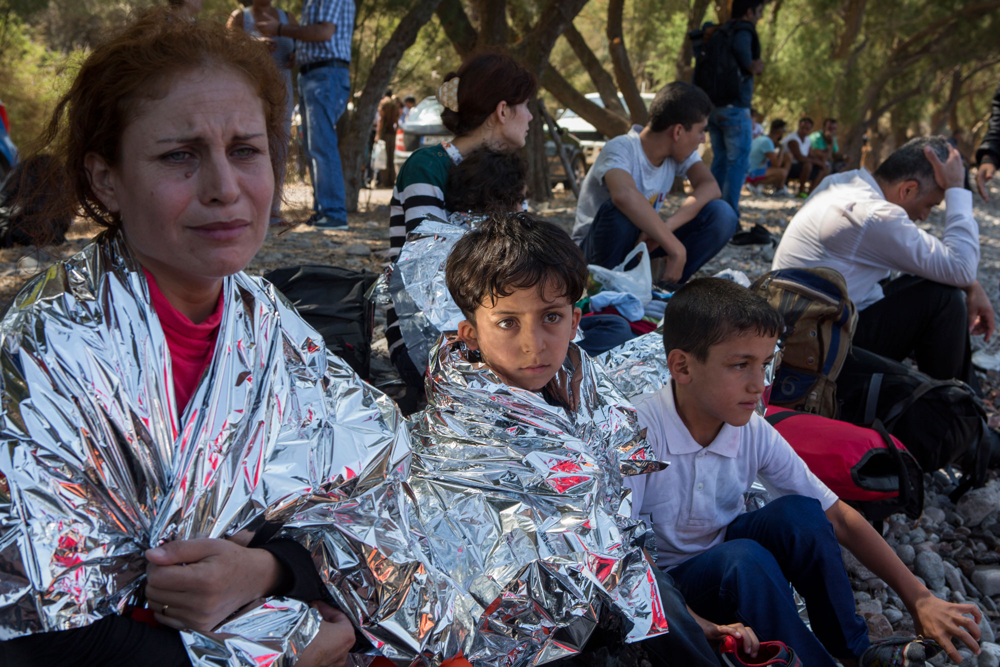 Photographer: Ivor Prickett | 6-year-old Syrian refugee Sarwan from Kobane sits alongside his mother and brother wrapped in an emergency blanket moments after the family had a terrifying end to their journey to Lesbos.   The boat they were in burst and many of those onboard had to jump into the sea and swim ashore.