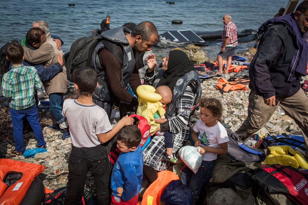 Photographer: Ivor Prickett |       35-year-old Osama and his wife Kald from Syria talk on the shore line after arriving to Lesvos with their 6 children.
