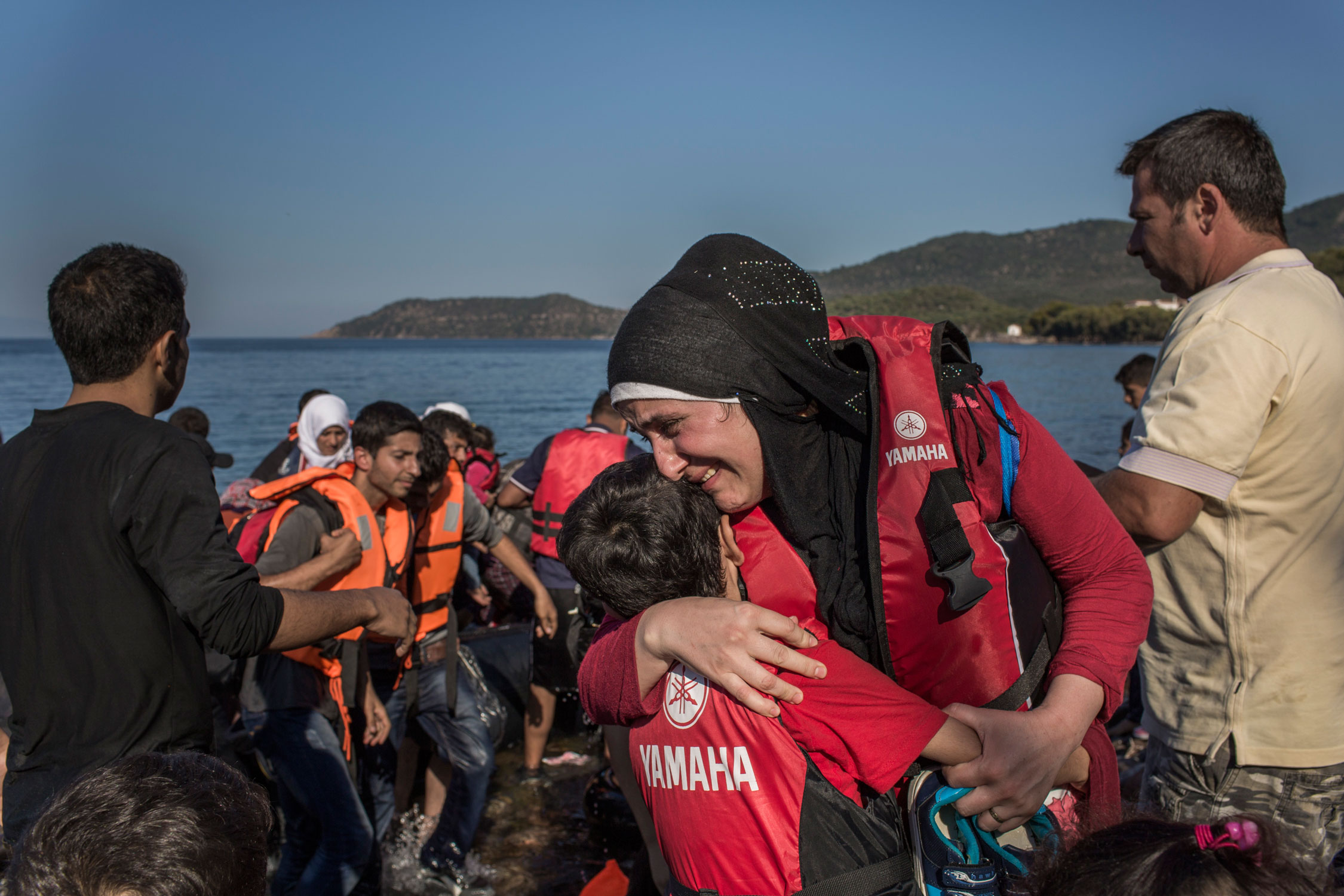 Photographer: Ivor Prickett |Syrian refugee Layla from Aleppo cries tears of joy as she hugs her 8-year-old son Lawand after they and their family reached Greek shores having crossed the Aegean from Turkey.