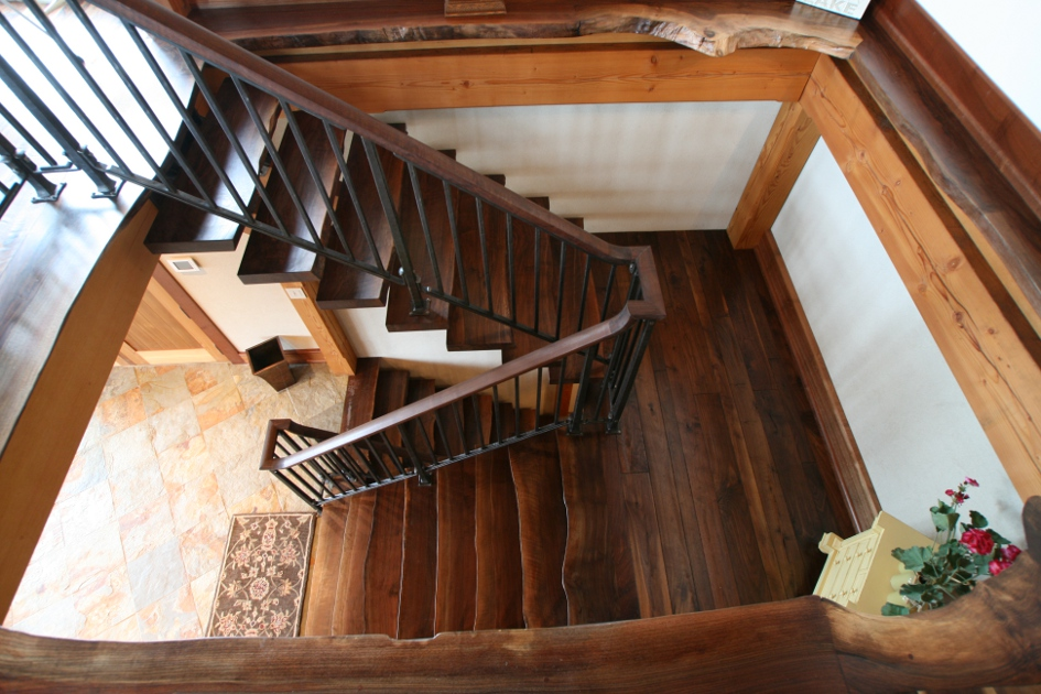 "Custom crafted walnut stairs feature live edges and appear to ""float"" on metal brackets and reclaimed Douglas fir stringers."