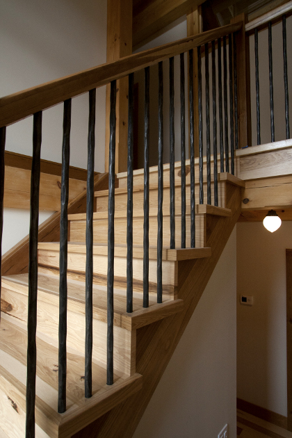 Fresh sawn hickory was paired with hand forged metal for this Upstate NY timber frame home's staircase.