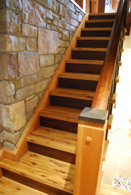 Reclaimed hickory treads join walnut raisers and a wanut railing for a custom staircase at Faywood Farms.