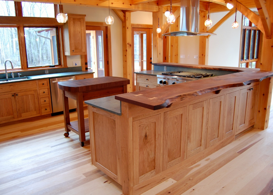 Butternut cabinetry is topped with live edge walnut countertops and rolling chop block island.
