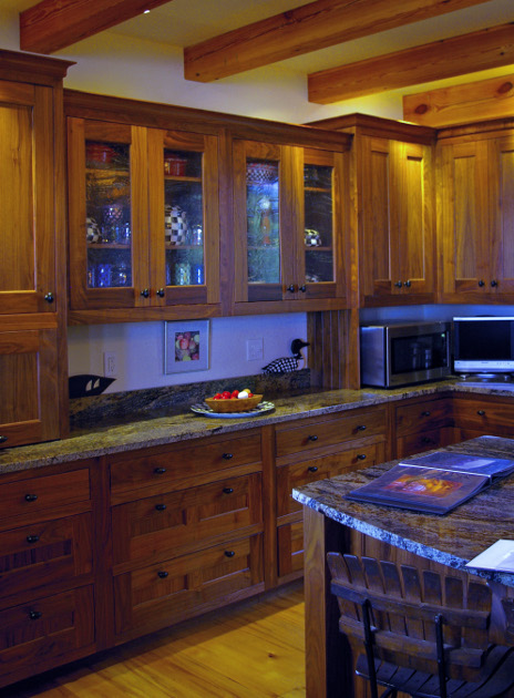 This cabinetry combines solid walnut insets and glass insets.