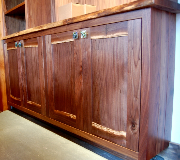 This custom walnut bar cabinetry features live edge stiles and one-of-a-kind pulls.
