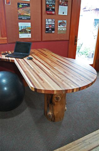 Multiple wood species come together as narrow strips to form this office desk countertop complete with a peeled log base.