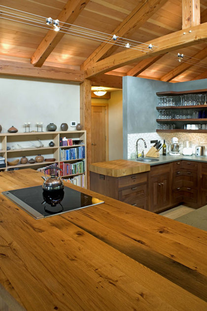 Crafted of reclaimed oak, this countertop includes a built in stove and joins an additional work space of natural slate.