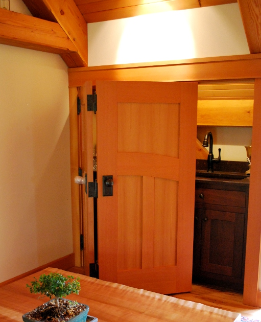 Folding Douglas fir doors collapse to reveal a mini bar in the loft of a Kentucky timber frame home. D36