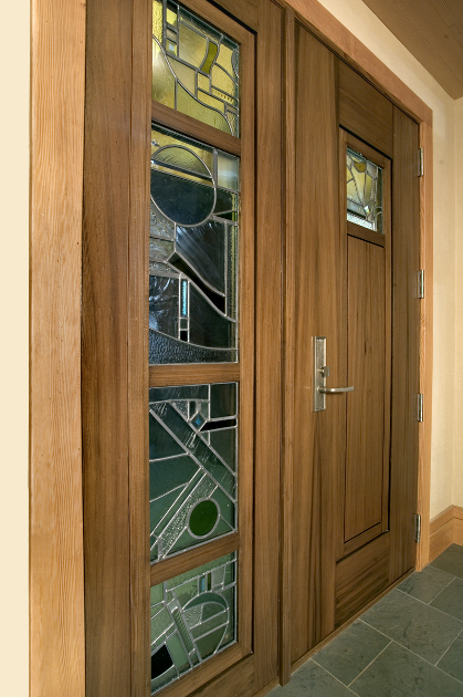 Crafted of reclaimed cypress, salvaged from rivers, this entry door features a custom stained glass sidelight and center window. D5