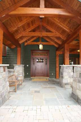 Timber frame entry porch with custom door.