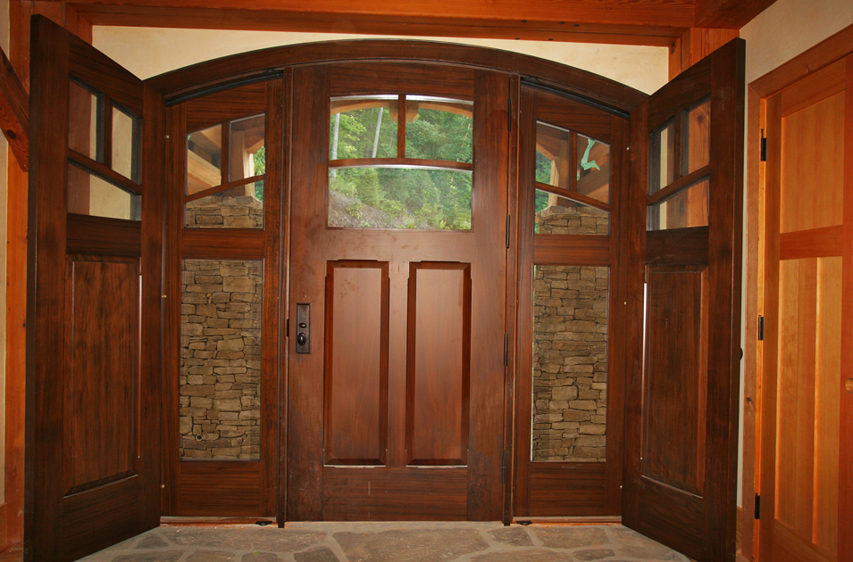 This custom crafted walnut door includes unique two part sidelights - the outer layer are screened while the inner layer are solid.