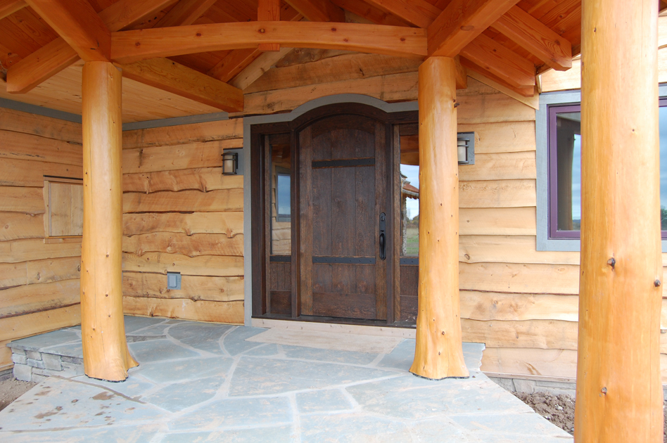"Fondly referred to as a ""castle door"" this Mendon home entry features heavy metal strapping across stained, reclaimed oak."