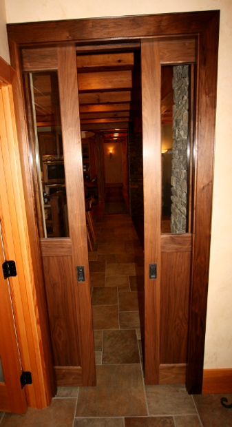 Custom walnut pocket doors feature windows and contrast with Douglas fir trim.