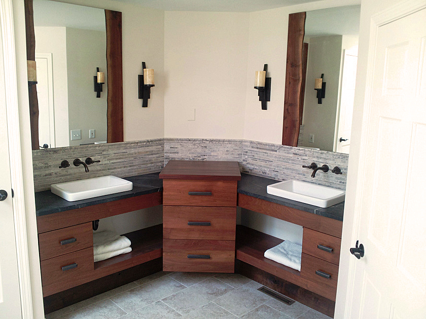 Reclaimed walnut his and her vanities are paired with live edge framed mirrors.