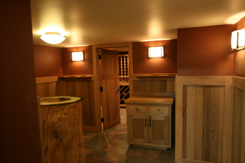 The wine tasting room of this lake home includes custom cabientry and wall paneling from reclaimed wine vats. W6
