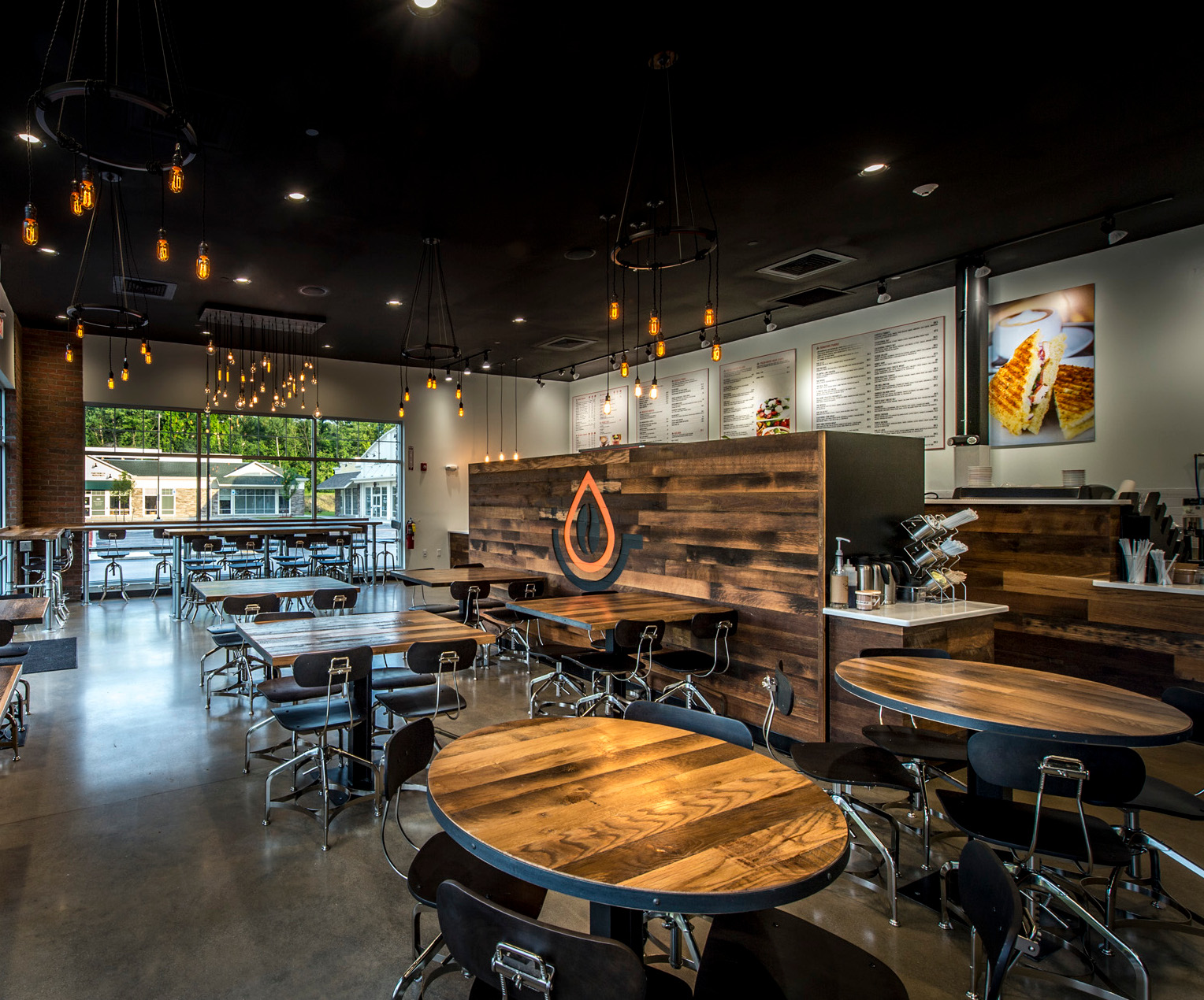 Inlayed within a wall of reclaimed mixed Settlers Plank hardwoods, the Pressed Cafe orange and black logo serves as focal point and separation of the ordering area from the dining space.