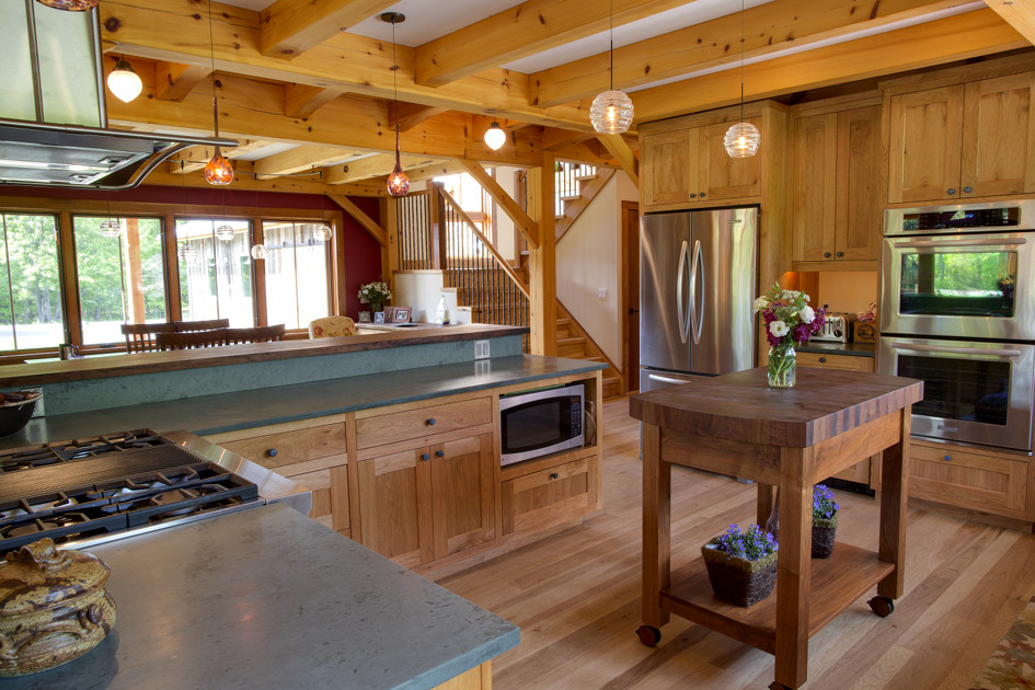 Butternut cabinets are joined by a walnut island with chop-block top in a timber frame home by New Energy Works.