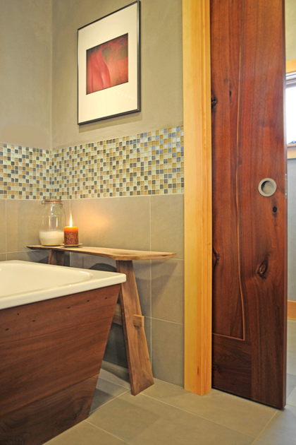 A walnut pocket door affords privacy between the bath and toilet area in a Portland OR home. D6