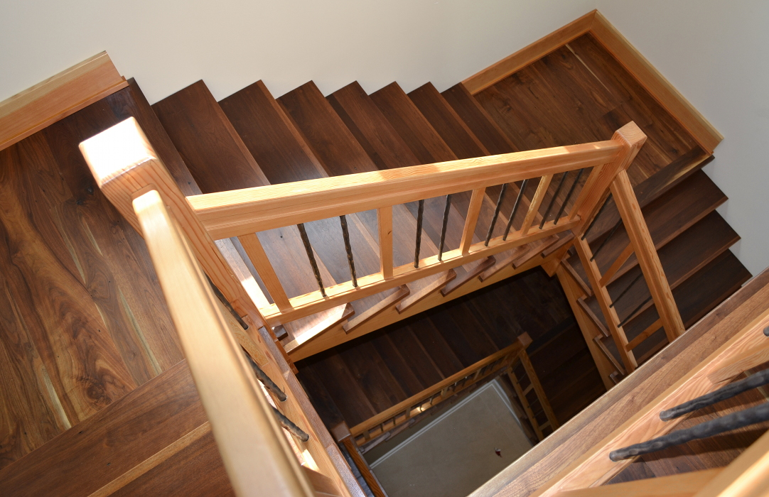 Walnut treads and landings join Douglas fir risers and railings to join two levels of a New York home.