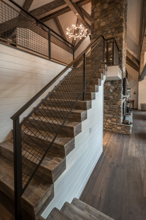 Custom-finished timber stairs in a Finger Lakes cottage home lead the way to an upstairs loft space.  ©  Scott Hemenway