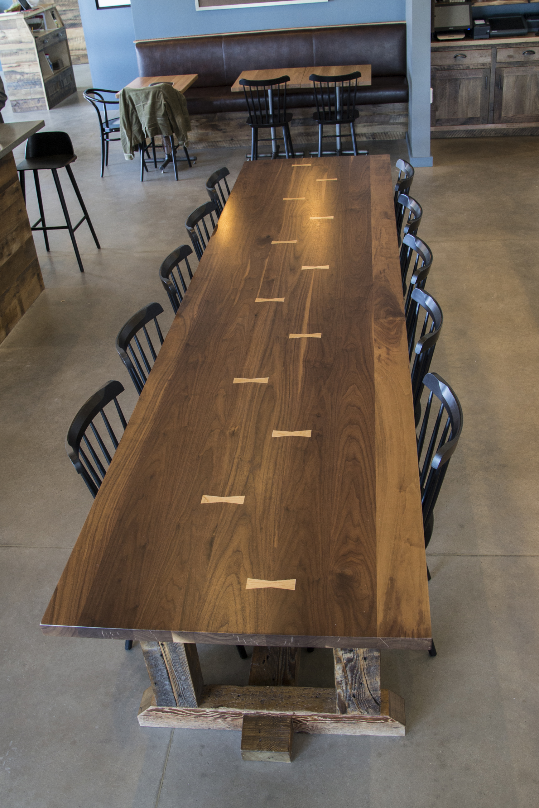Walnut top table features butterfly joinery with a trestle base of reclaimed Hemlock