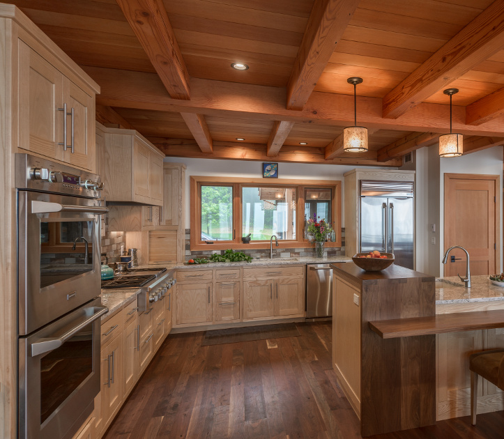 Kitchen cabinetry crafted from Ash with Walnut accent tops, include a 'waterfall' of Walnut. Photo Scott Hemenway.