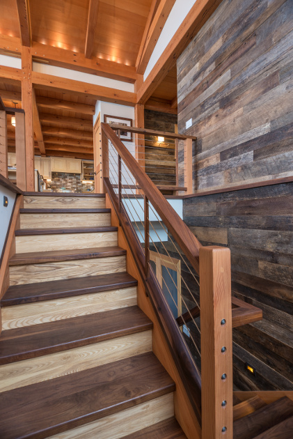 Reclaimed walnut treads join reclaimed elm risers and a Douglas fir railing posts in this timber frame home. Photo Scott Hemenway.