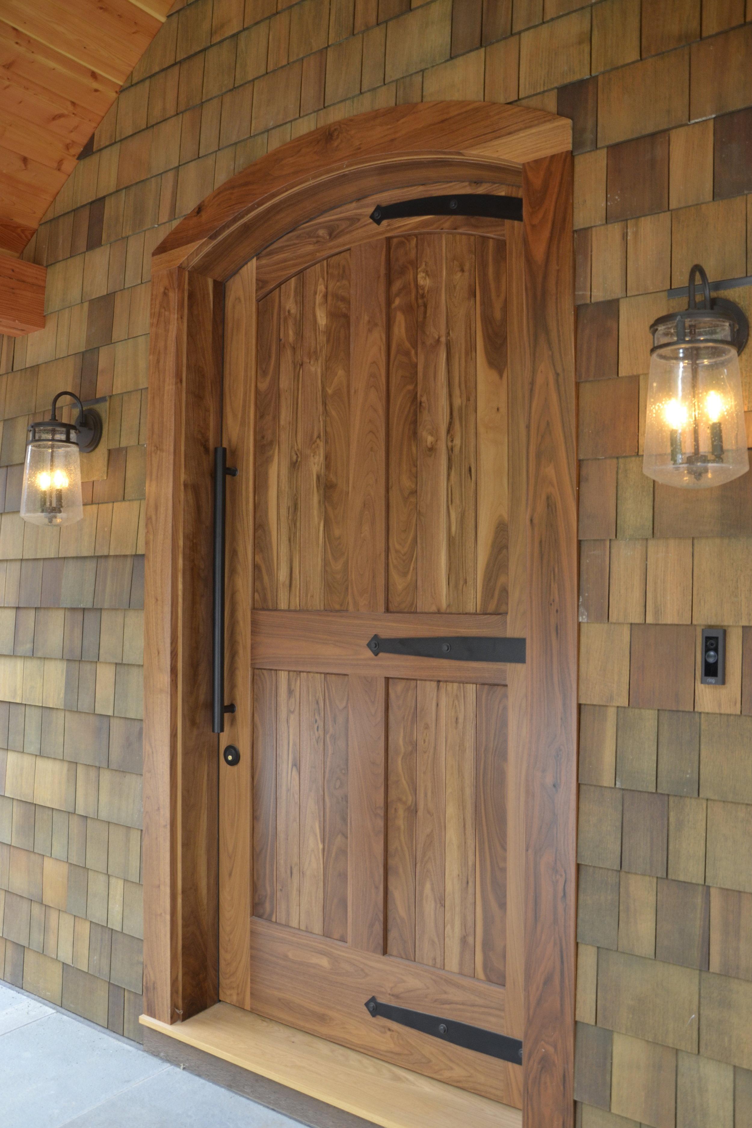 Massive Walnut entry door with custom metal hinges