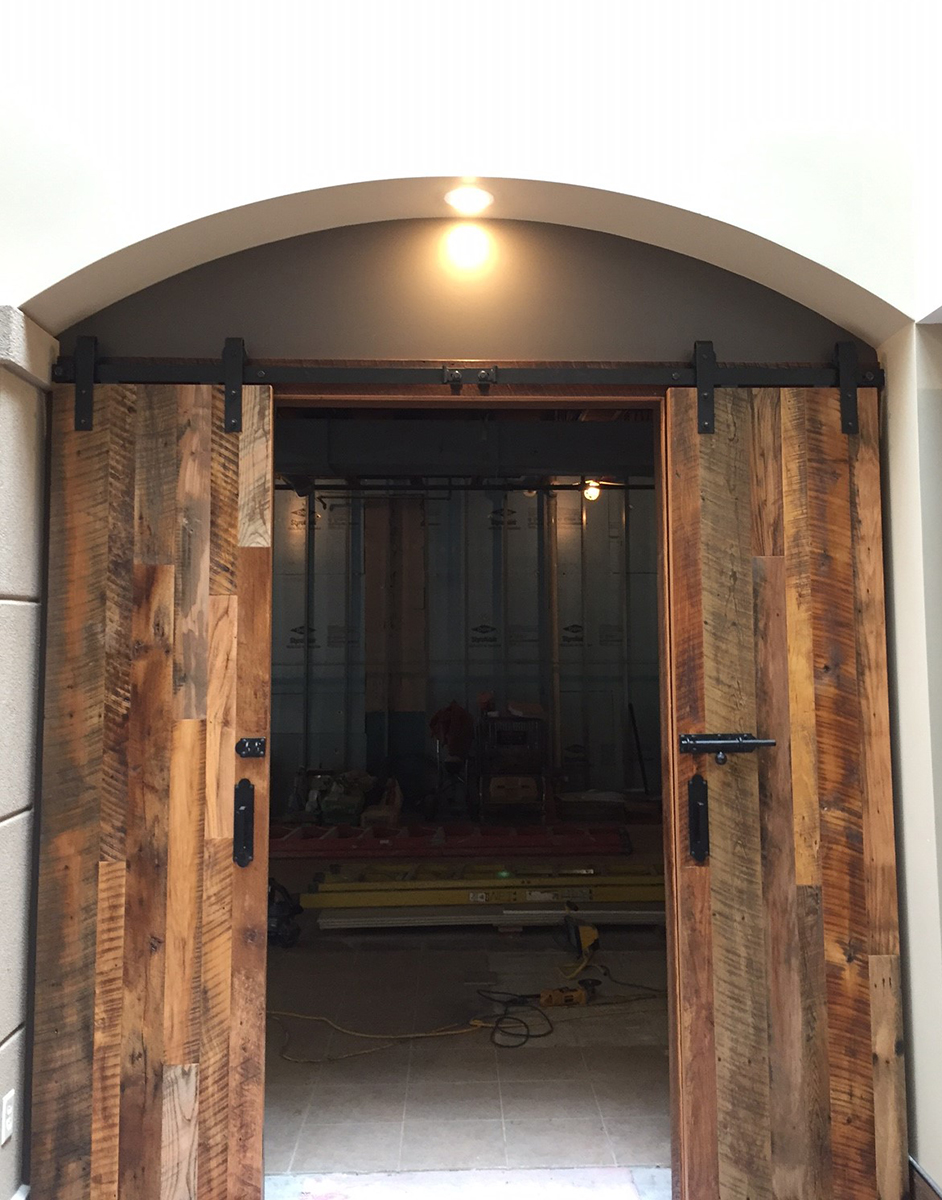 Flat track door with center opening and bolt lock. Wood is reclaimed mixed oak.