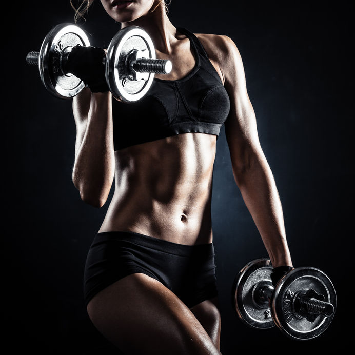 Toned woman lifting dumbbell weights