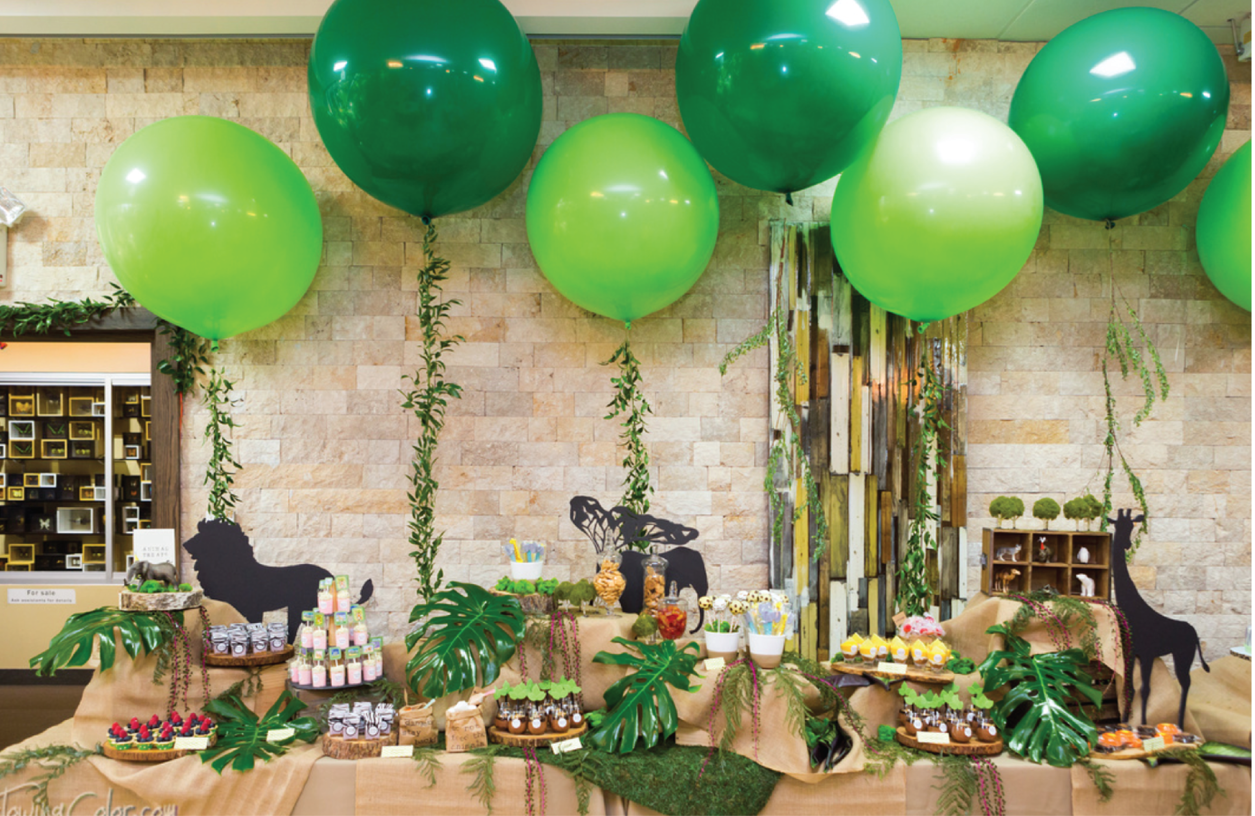 Here is the full shot of the Dessert Table. As you can see we used a lot of real plants to make it come to life. Even the vines on the balloons are made with fresh leaves.