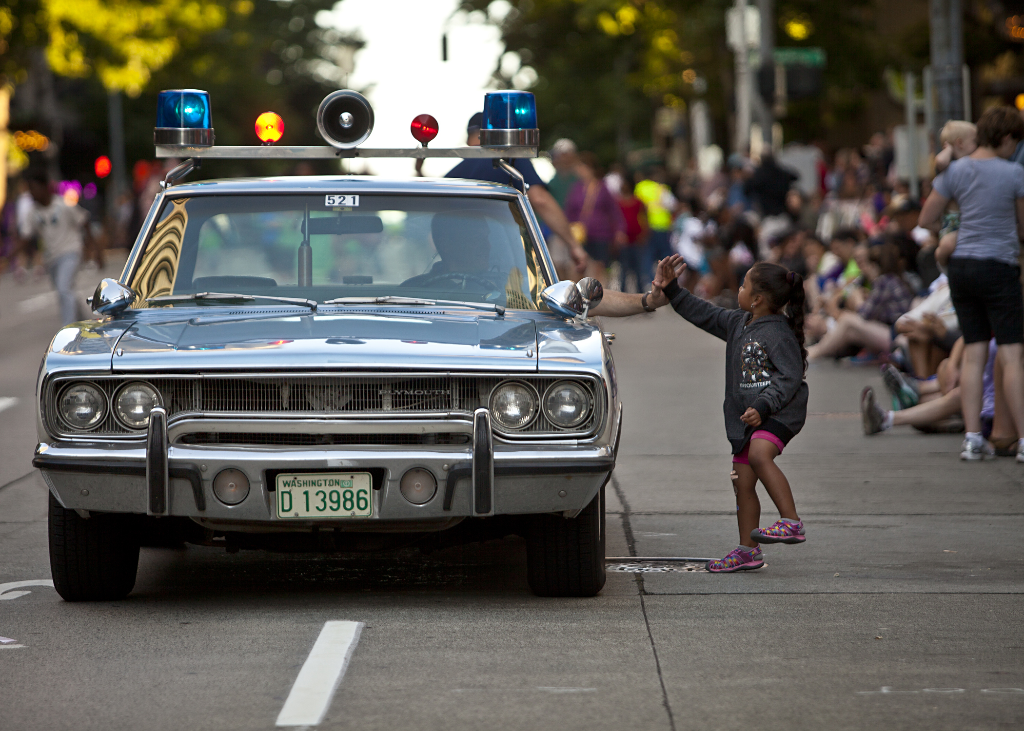 One little girl offers a Seattle Police Officer a high-five during the 2014 Torchlight Parade.