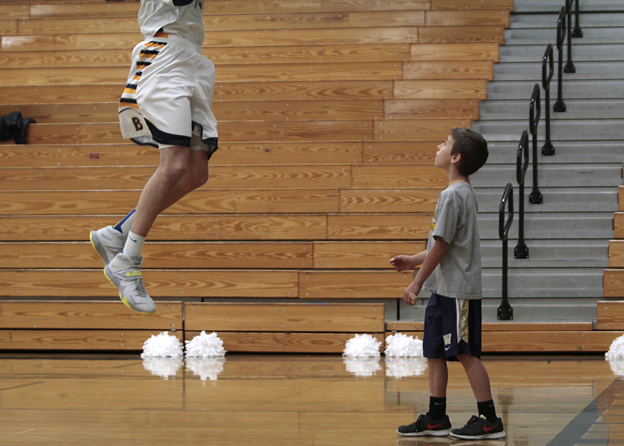 Cade Orness, 8, son of Bainbridge High boys basketball Head Coach Scott Orness, gets closer than the average fan as he watches from under the net as a player goes up for a rebound during a warm-up session.