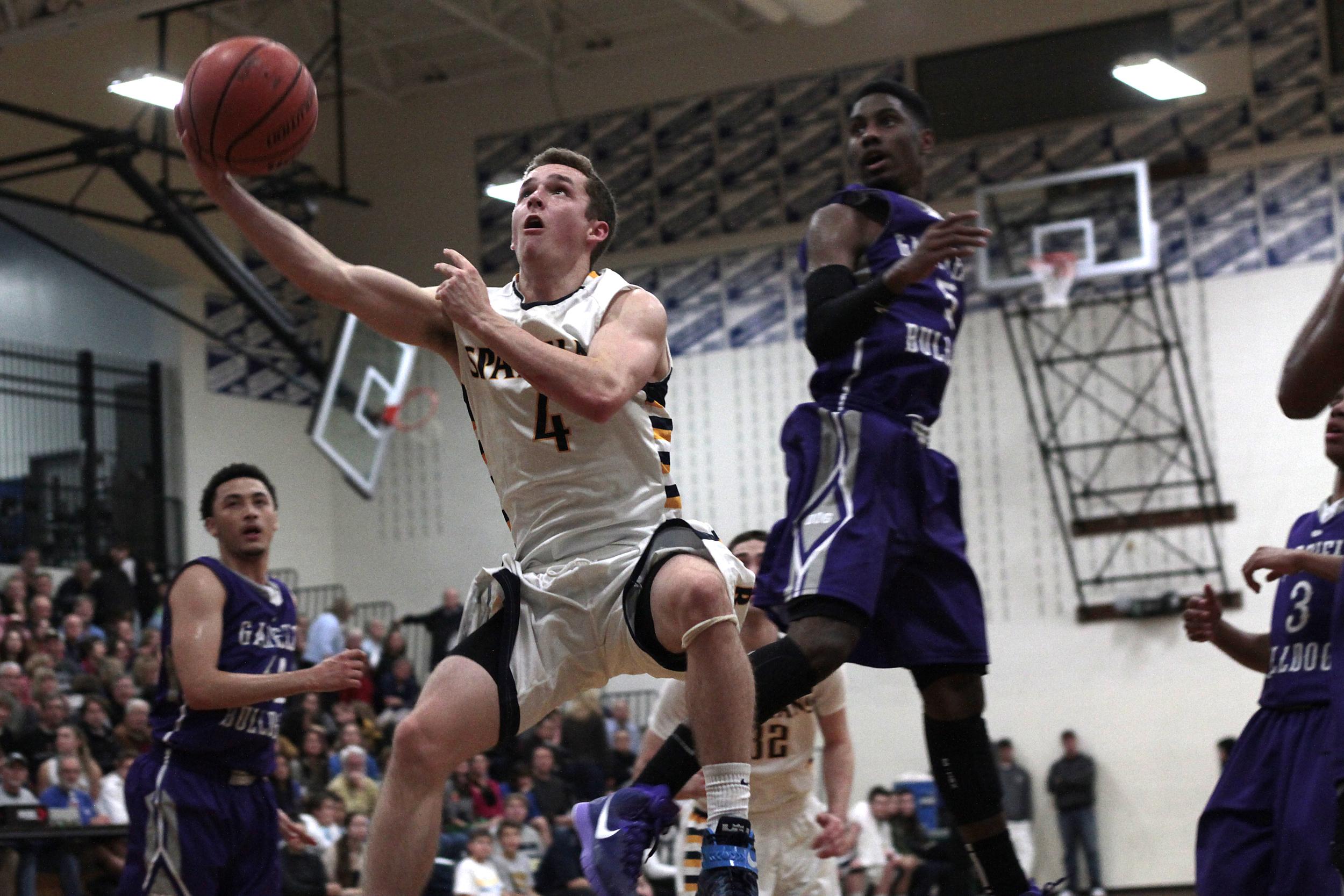 Bainbridge High School senior Blake Swanson reclaims the ball in the air during a high-flying basketball battle against Garfield High.