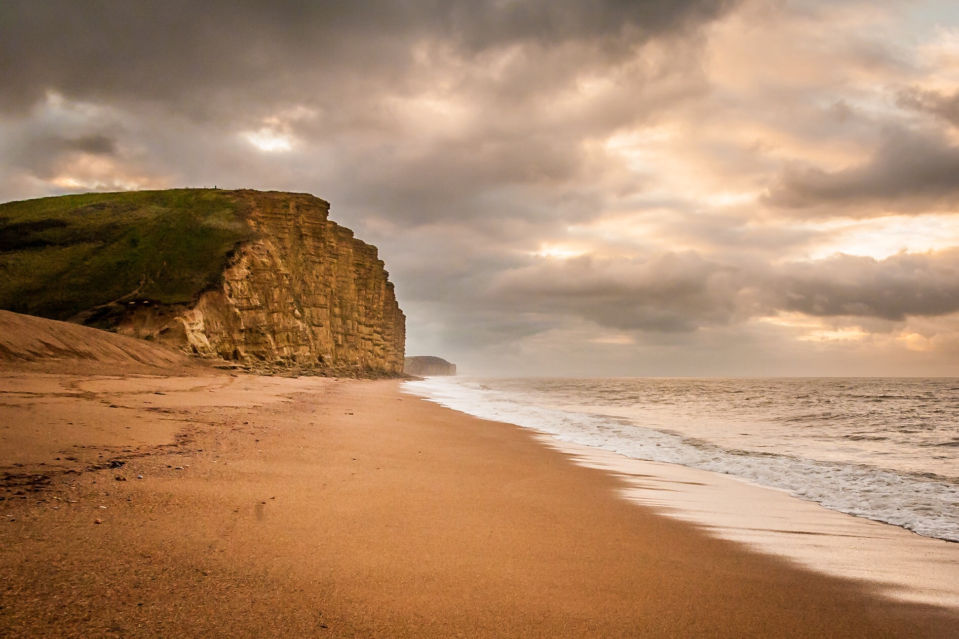 West Bay beach and cliffs  Once described be me as Gold Cap (I know it should be Golden Cap), this is actually the view looking the other way from West bay beach, towards Burton Bradstock. Another great Dorset view with lots going on in the sky and a very enticing beach leading to those lovely golden cliffs.