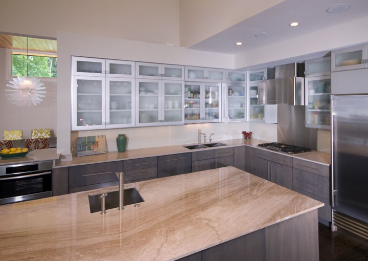 The backsplash in this modernist motif kitchen is solid sheets of glass over painted walls which adds to the simplicity in a subtle and unexpected fashion.