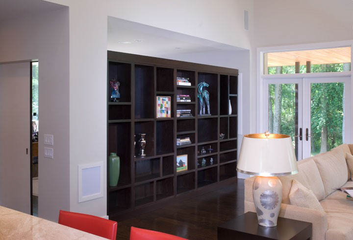 This custom made bookshelf divides the owners proves study from the great room. Carefully placed peek-a-boo pass-throughs keep it from being a monolithic divide.