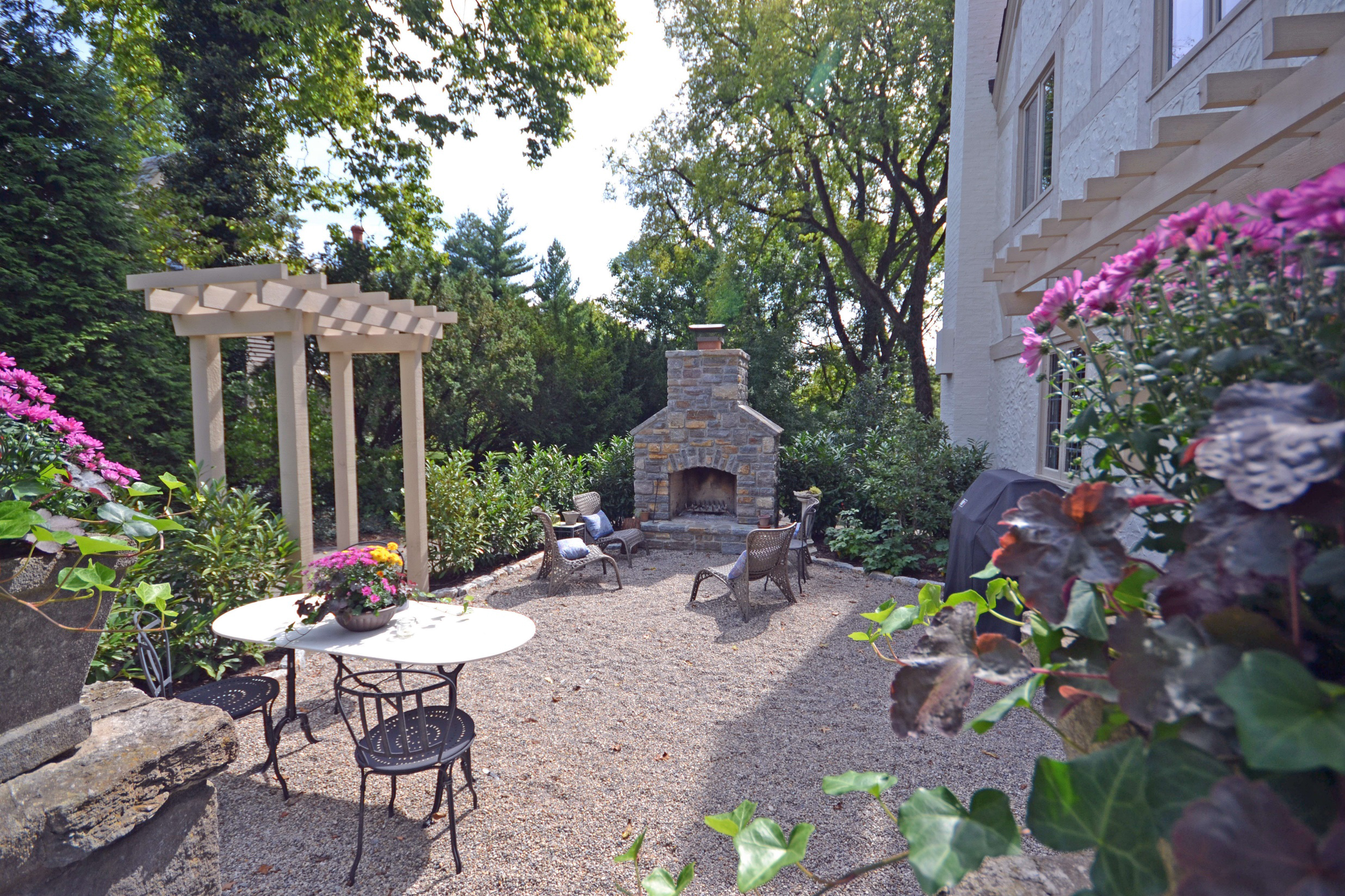 """The """"before"""" of this area was overgrown honeysuckle bushes and trashcans…the after is a useful and verdant courtyard topped with smooth-to-the-foot French pea-gravel."""