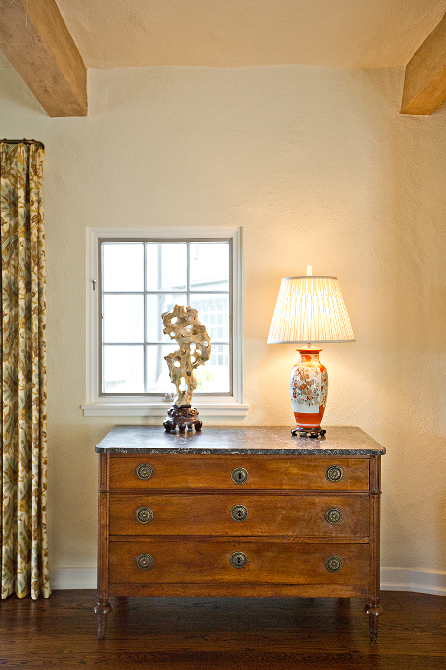DIGS'designers will always advocate for harmony when it comes to adding visual interest. Here, the French Regency walnut commode echoes the wood ceiling beams. Framed with natural light, the Chinese Scholars rock positively glows.