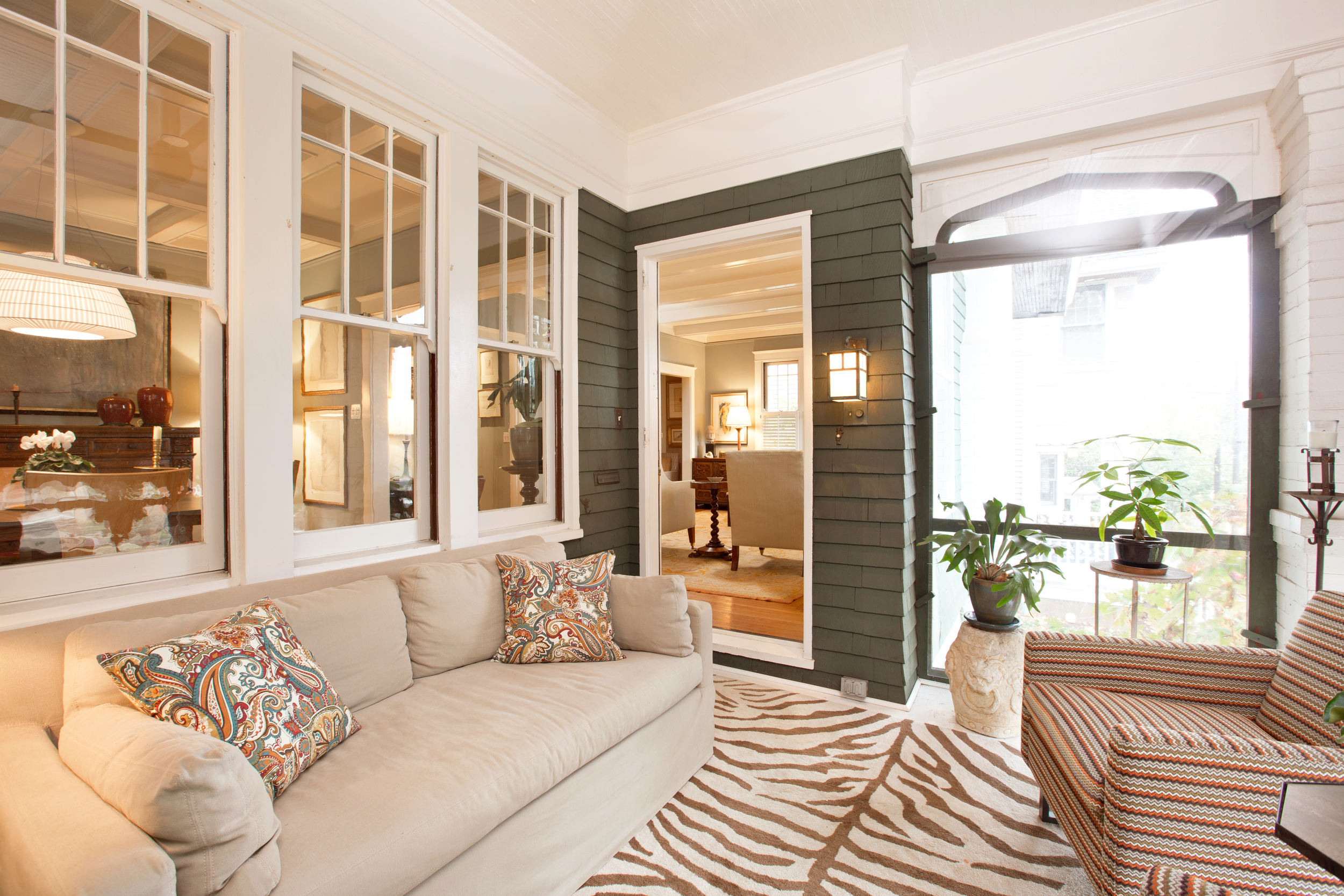 """We may have to break our """"no loitering"""" rule for this   screened   porch.  E  ase   (all fabrics are outdoor rated)  and sophistication   combine to make this    one heck of a relaxing,  bright and   welcoming  space  to while away summer days."""