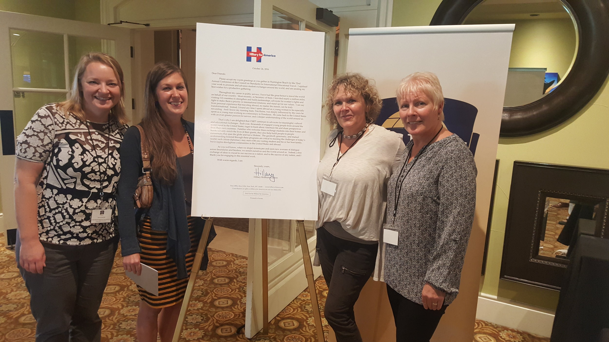 SHARE! staff at CSIET meeting, 2016 with a letter from Hillary Clinton supporting student exchange.