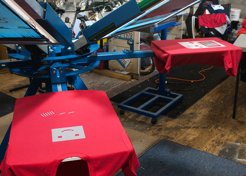 Shirts on press at different stages of the print