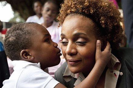 Le jeune Johan embrasse Michaëlle Jean lors d'une visite officielle dans un orphelinat de Santo Domingo, en République dominicaine. Le garçon a survécu à huit jours sous les décombres, avant d'être rescapé.  photo : Paul Chiasson, Presse canadienne.